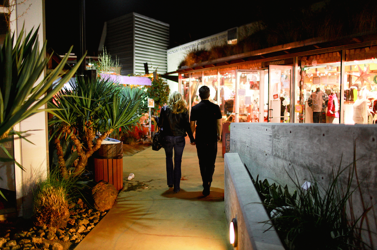 A couple holding hands shopping at The CAMP at night in Costa Mesa.