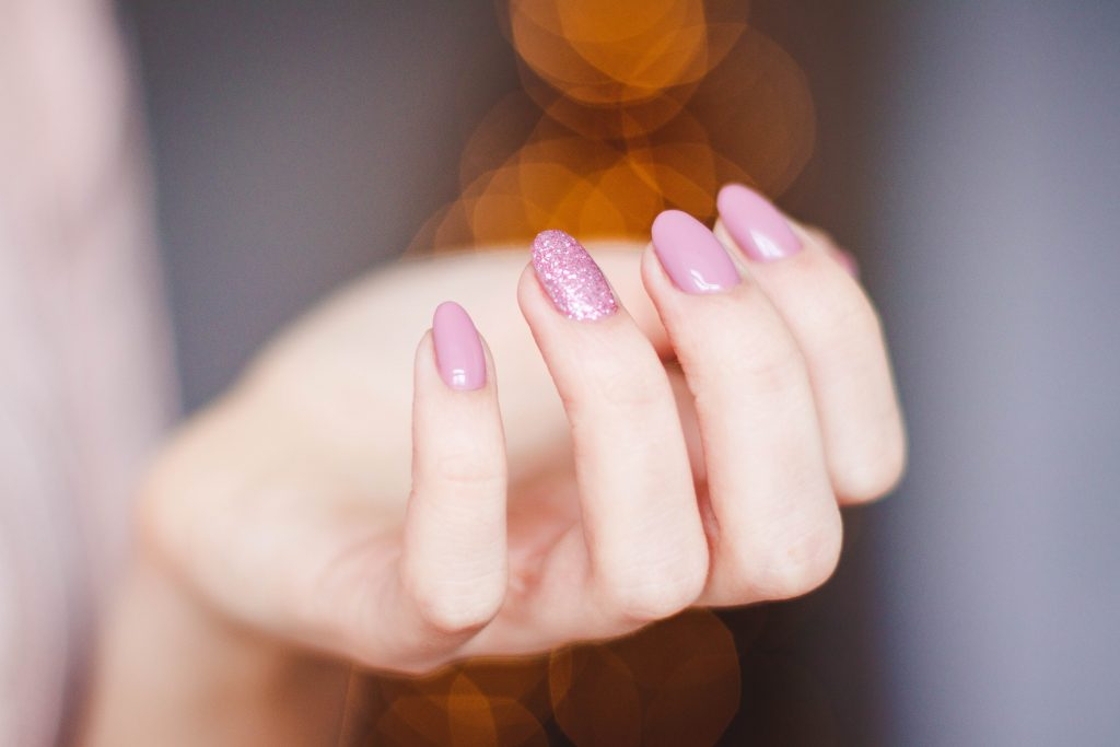 woman's hand with pink manicure
