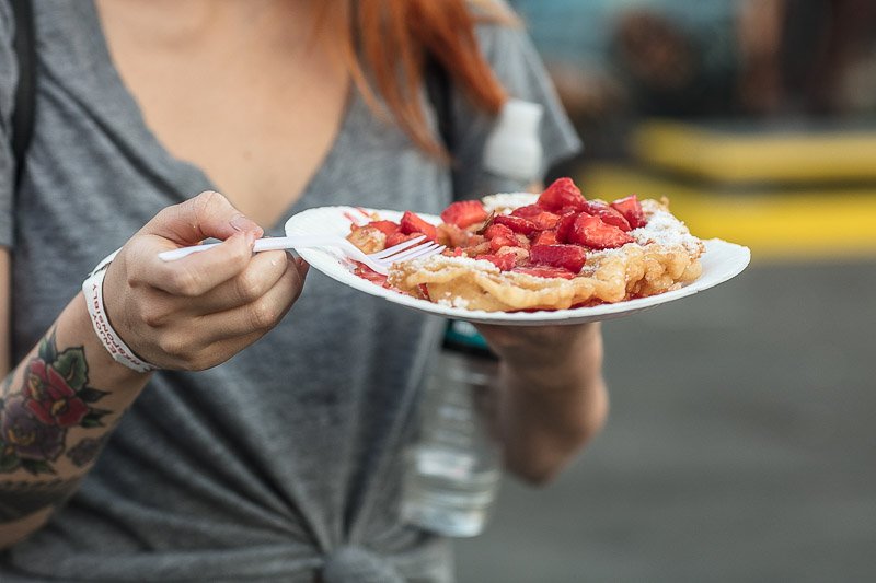 Woman holding funnel cake at the OC Fair.